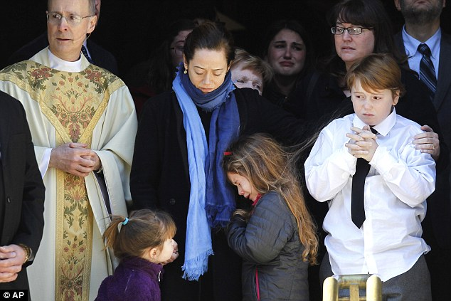 Sad: Mimi O'Donnell, center, comforted her daughter Tallulah, along with daughter Willa, left, and son Cooper, at the emotional ceremony