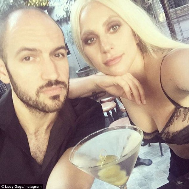 Flashing: Gaga is seen wearing a lacy half-cup bra with a traditional martini at the forefront, as she leans on the shoulder of a male friend seemingly inside the venue