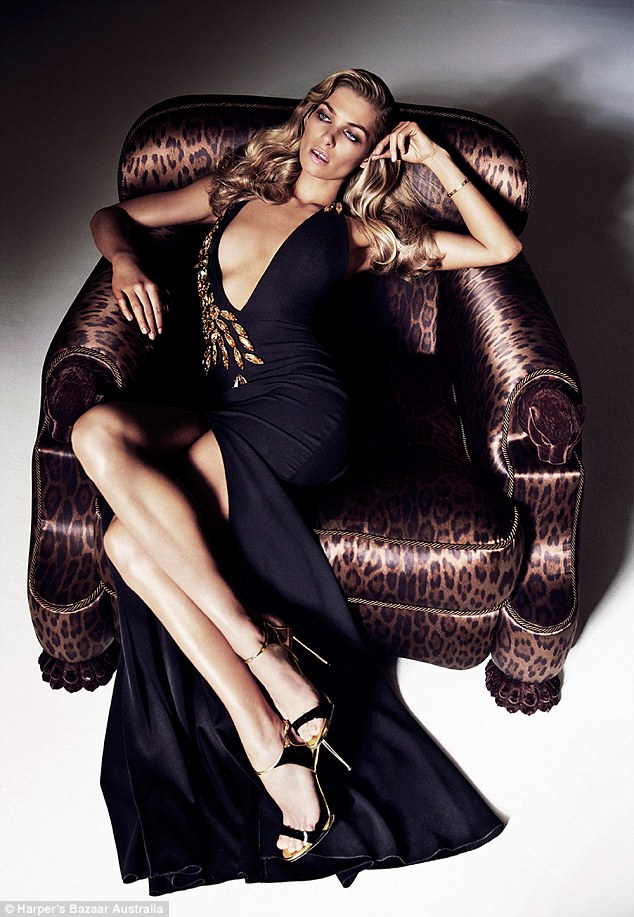 Doing what she does best: In another shot, the glamazon is seen looking off into the distance as she reclines again on a sofa wearing a deep plunge neck gown by Australian designer Alex Perry