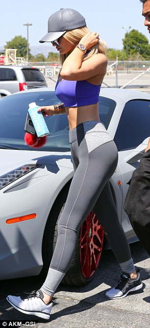 Pretty in purple: Kylie wore a bright purple sports bra, which highlighted her toned abs