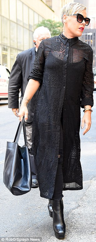 Edgy: The star wore a long lacy blouse, distressed skinnies, and sky-high platform boots