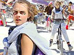 EXCLUSIVE: Cara Delevingne was spotted attending the 'Burning Man' Festival in Black Rock City, NV. The actress and super model looked striking as she rode her customized bike through the hot desert.