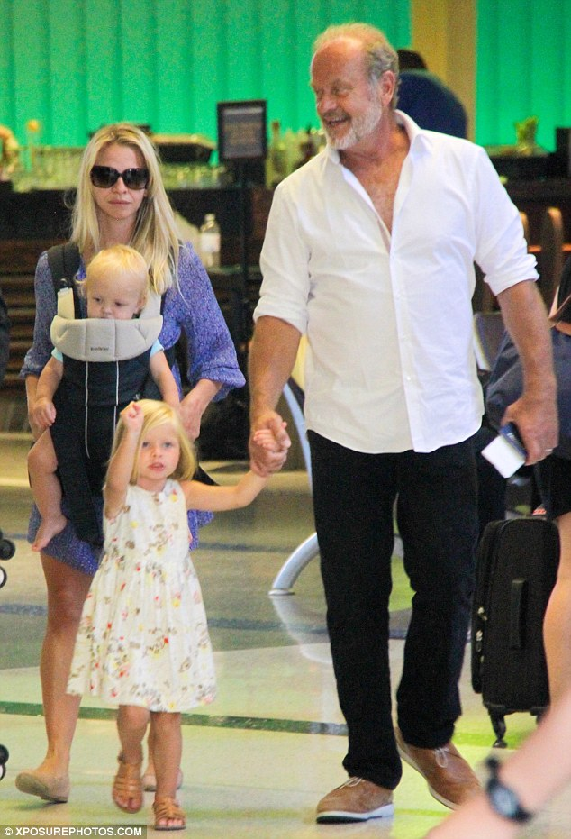Doting dad: The 60-year-old actor appeared to be very happy to be joined by his three-year-old daughter as they held hands on the trip