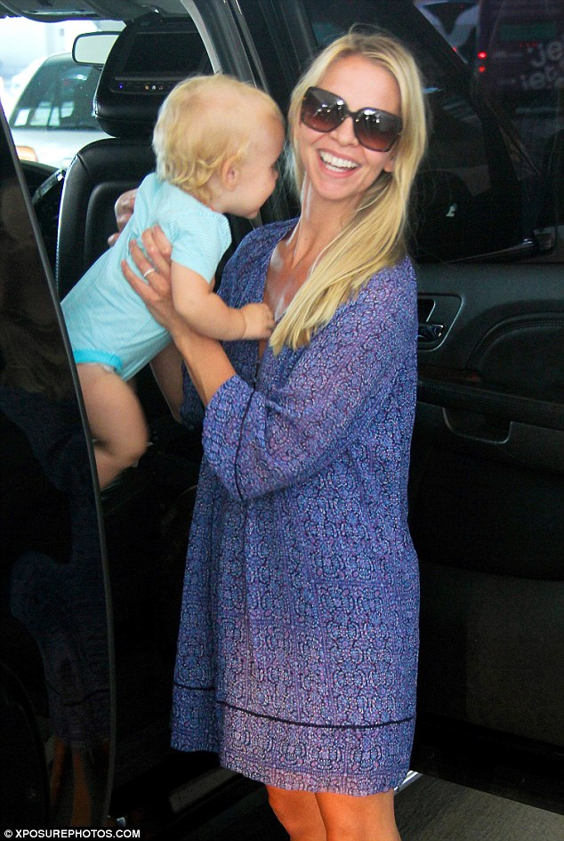 Beaming: She smiled big when grabbing the adorable youngster from his car seat
