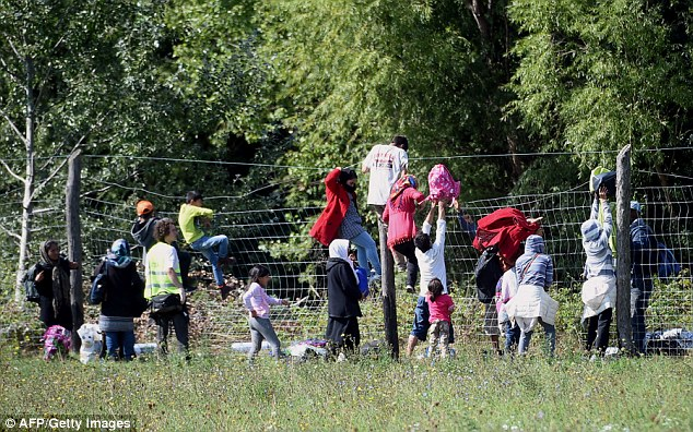 Men, women and children climb over fences with their belongings after breaking through a police cordon today