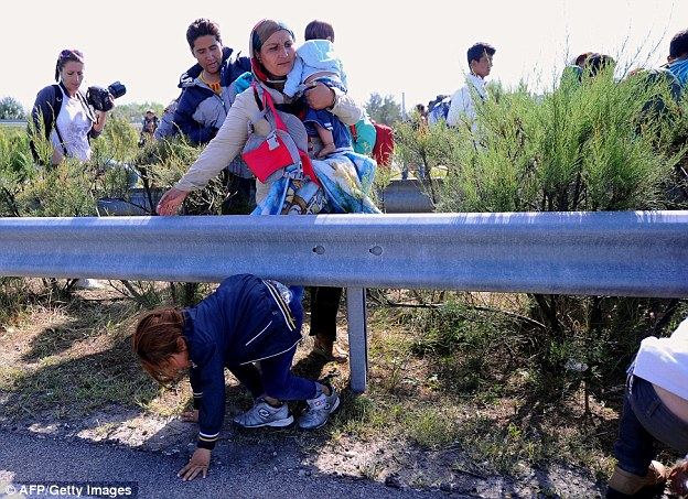 A migrant family walks across the middle lane of M5 highway after they broke through a police cordon