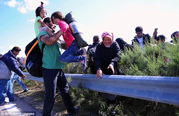 A migrant family clambers across the middle lane of M5 highway close tothe Hungarian-Serbian border