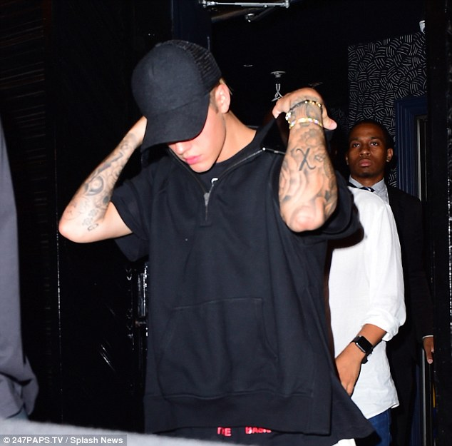 Low profile: Bieber kept his face concealed in a low baseball cap on the night