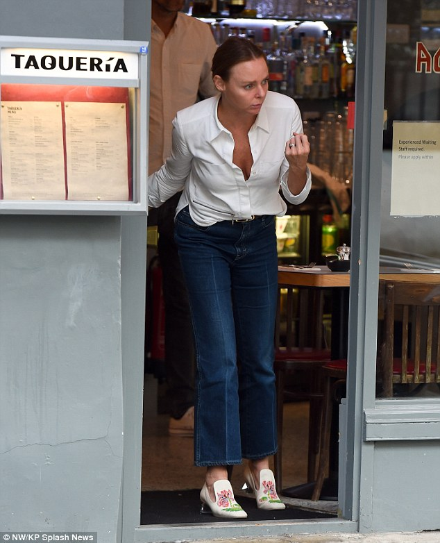 She's in fashion: Stella, 43, looked effortlessly chic in flared jeans, styled further with a plunging white blouse