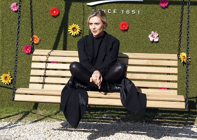 Fun! Against a bright and cheerful floral background, Elizabeth sat cross-legged as she continued to take snaps at the daytime press event