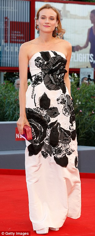 Standing tall: She expertly teamed the dress with satin heels made out of the exact same shade, while styling the getup further with a crimson coloured clutch and jewelled drop-down earrings