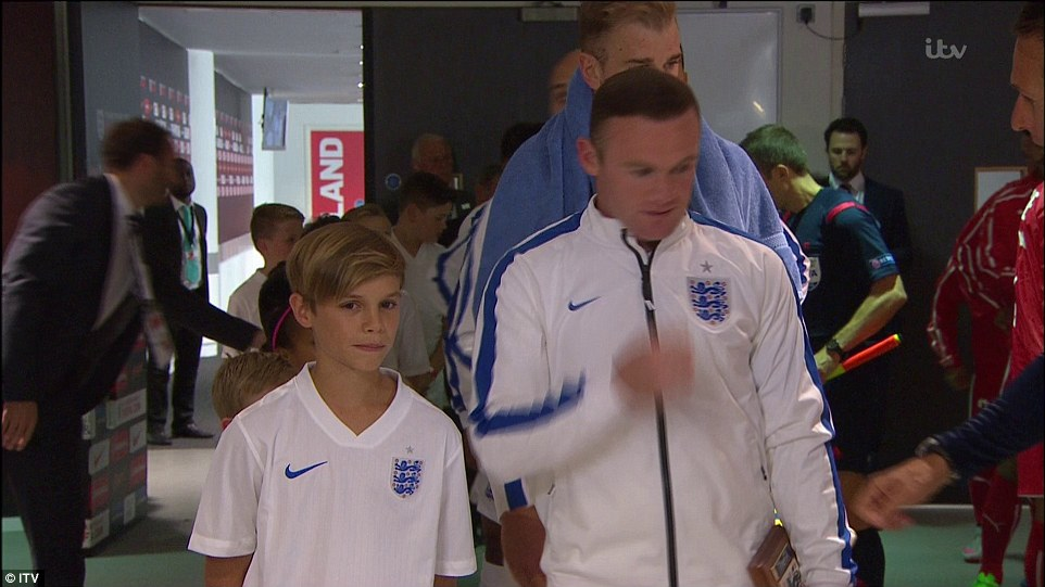 Romeo, who is the second eldest of David Beckham's four children, waits in the tunnel alongside Rooney before kick-off