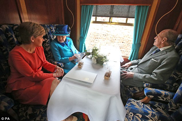 Don't forget who's the real Queen of Scots: Her Majesty chats with First Minister Nicola Sturgeon as Prince Philip enjoys the view from the carriage on their steam train