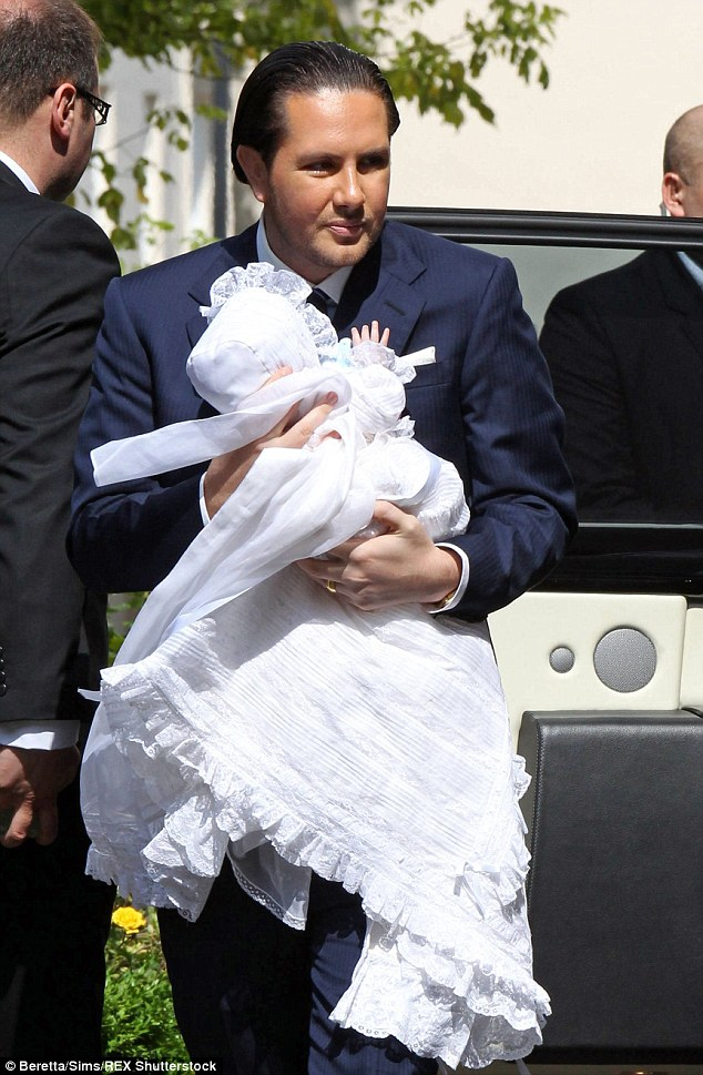 Modern man: Mr Stunt with one of his twin sons at their christening last Sunday