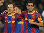 Barcelona's midfielder Andres Iniesta (C) and Barcelona's midfielder Xavi Hernandez (R) celebrate after scoring during the Spanish league football match opposing FC Barcelona and Racing at the Camp Nou stadium in Barcelona on January 22, 2011.       AFP PHOTO/ LLUIS GENE (Photo credit should read LLUIS GENE/AFP/Getty Images)