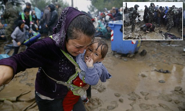 Thousands of migrants battle with riot police in Macedonian quagmire