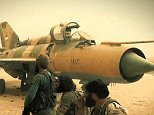"""In this image posted on the Twitter account of Syria's al-Qaida-linked Nusra Front early Thursday Sept. 10, 2015, which is consistent with other AP reporting, fighters from the group gather around a Syrian government forces aircraft, inside the Abu Zuhour air base, in Idlib province, north Syria. After a two-year siege, al-Qaida's affiliate in Syria and other insurgents on Wednesday captured the one remaining Syrian army air base in Idlib province, a development that activists said effectively expelled the last of President Bashar Assad's military from the northwestern province. The Arabic words in the bottom picture reads: """"from inside Abu Zuhour air base."""" (Al-Nusra Front social media account via AP)"""
