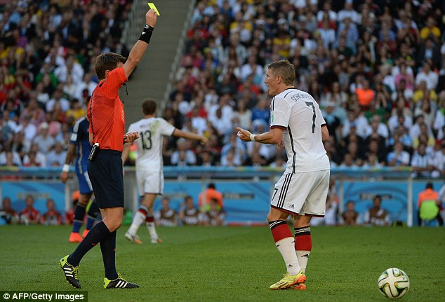 Proceed with caution: Bastian Schweinsteiger is shown a yellow card by referee Nicola Rizzoli