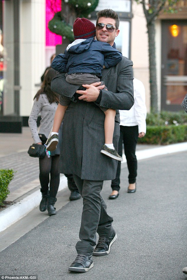 Sleepy: Robin carried his young son while out shopping on Saturday, as the boy had fallen asleep