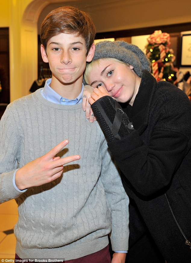 Feeling charitable: Miley Cyrus showed a surprisingly demure side as she attended the Brooks Brothers event to benefit St. Jude Children's Research Hospital  on Saturday where she posed with DJ Oscar Adler