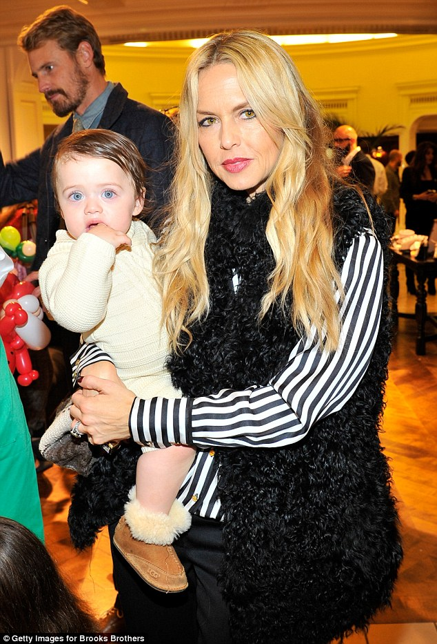 Bundle of joy: Rachel Zoe looked smart in a shaggy waistcoat while clutching her youngest boy Kaius