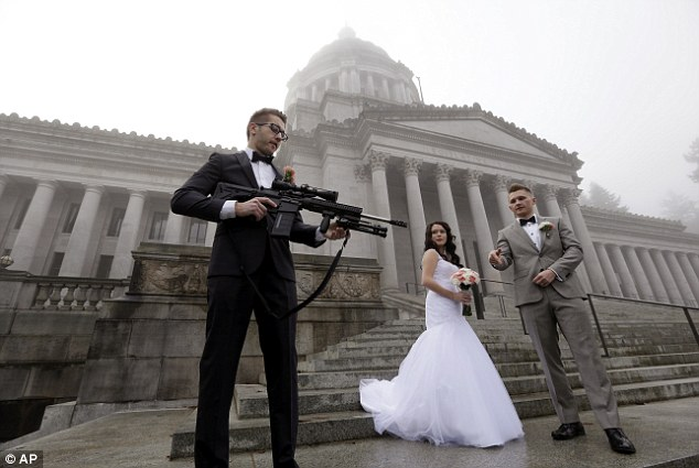 Locked and loaded: The best man then holds the weapon up as the couple watch