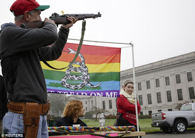 Taking aim: Jeff King (left) of Centralia, Washington points a rifle towards the state capitol. Initiative 594, which requires background checks for all gun purchases in Washington state, was voted into law last month