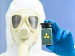 Person in bio-hazard suit and gas mask holding a radioactive isotope sample in a small green plastic jar. D9WGBX