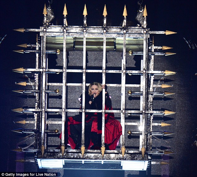 Locked up: She's seen encased in a cage, as well as later performing pared down acoustic versions of some her perkier 80s classics including Who's That Girl