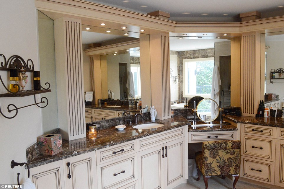 Ornate: The master bathroom has plenty of vanity space and features marble and stone custom showers and bath tub