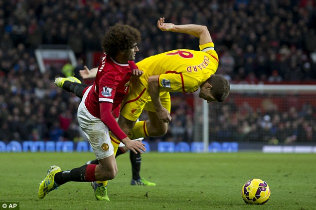 Marouane Fellaini (left) tussles for possession with Gerrard in the Premier League game at Old Trafford