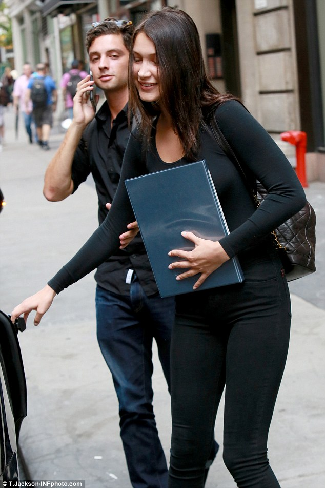 Following her sister's footsteps: Glossy brunette Bella looked perfectly groomed, as she hopped into a vehicle with a quilted backpack carrying her belongings and her model book in her hands