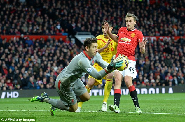 Jones (left) gets his hands to the ball under pressure from United forward James Wilson