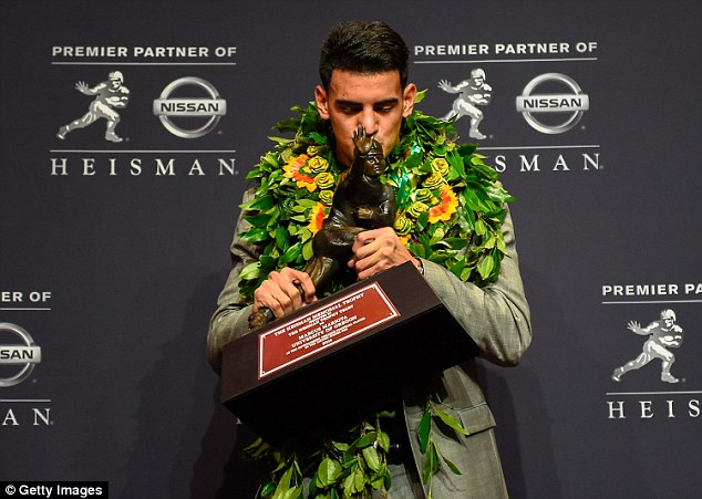 Kiss: Mariota, pictured at his trophy presentation ceremony at the New York Marriott Marquis on Saturday, is the first University of Oregon player and Hawaiian to win the award