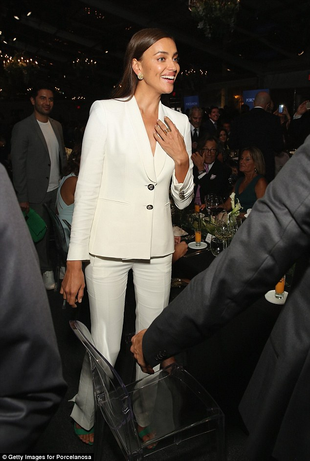 Hello everybody: Irina's friend held her bright green handbag while she mingled among the guests