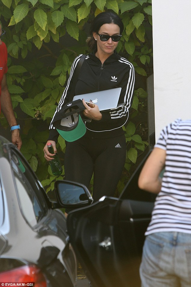 Sporty and comfortable: Katy was clad in an Adidas track suit featuring a sporty white-striped jacket and clingy black leggings