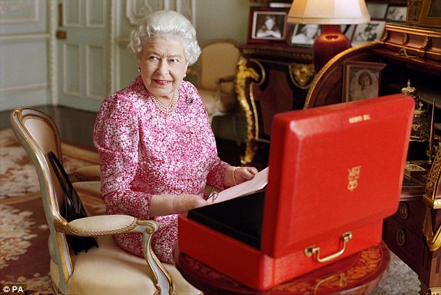 The Queen pictured at her desk in her private audience room at Buckingham Palace with one of her official red boxes