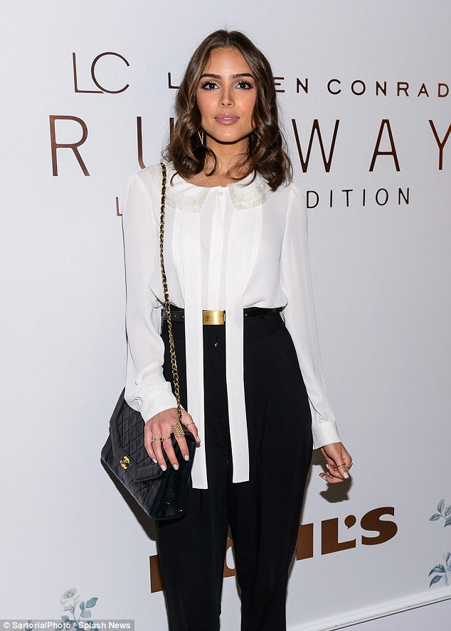 Understated: Olivia donned a monochromatic style in a scarfed white blouse and high-waisted black trousers