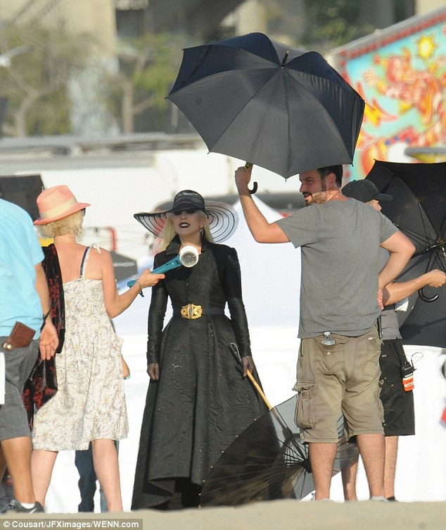 Cooling off: The platinum blonde was covered with a black umbrella thanks to an assistant