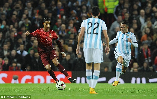 Ronaldo (left) runs with the ball for Portugal during a friendly against Argentina at Old Trafford