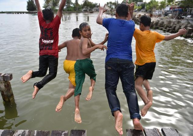 Children go for a swim at the Meulaboh traditional seaport in Aceh province on November 30, 2014