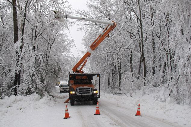 Green Mountain Power cuts limbs overhanging powerline in Waterbury, Vt., on Thursday, Dec. 11, 2014. Tens of thousands of electric customers across Vermont w...