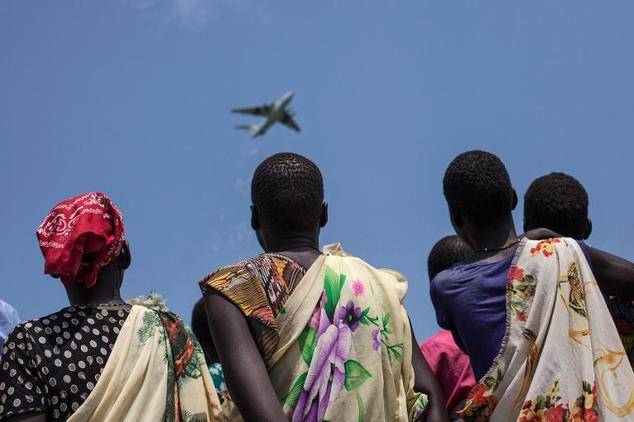 Women look at an airplane of the International Red Cross as it drops emergency food supplies in Leer, South Sudan, on July 5, 2014