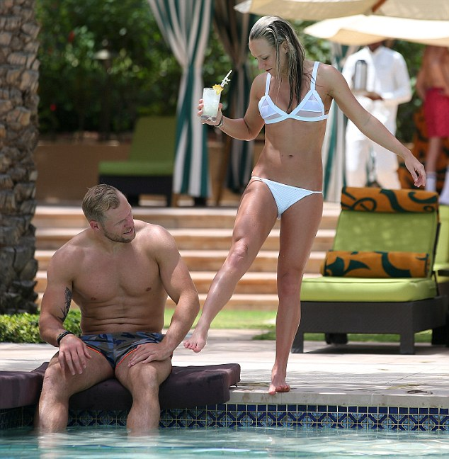 Bronzed: Chloe cheekily gave her beau a kick as she inspected her deep brown tan