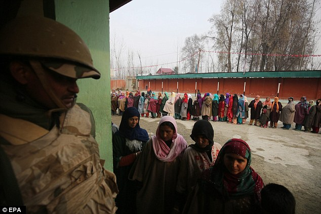 An Indian paramilitary soldier stands guard as women wait  in a queue to cast their votes just outside Srinagar