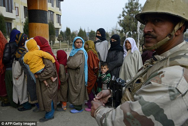 An Indo-Tibetan Border Police (ITBP) member stands guard as voters queue at a polling station in Srinagar