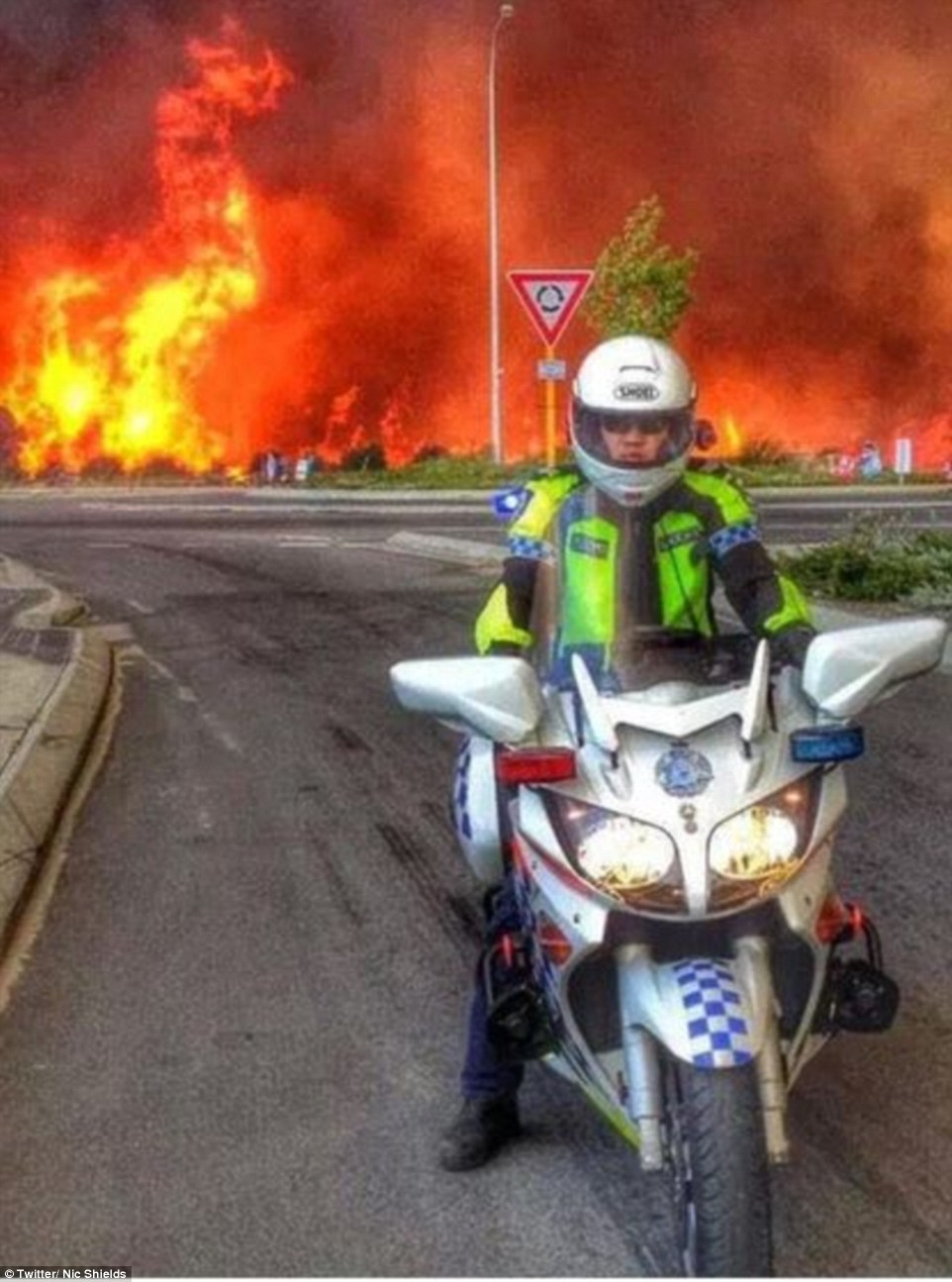 A police man stands guard at Whiteman Park after a vicious fire raced through the Perth suburb
