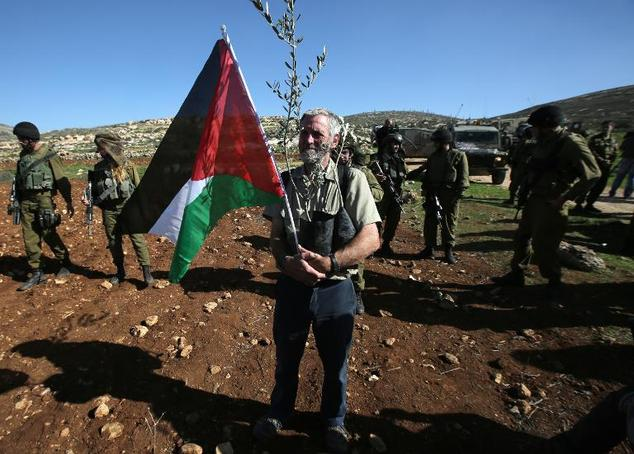 A man holds a Palestinian flag and a baby olive tree during a demonstration intended to plant 300 olive trees in the village of Turmus Aya near Ramallah, in ...