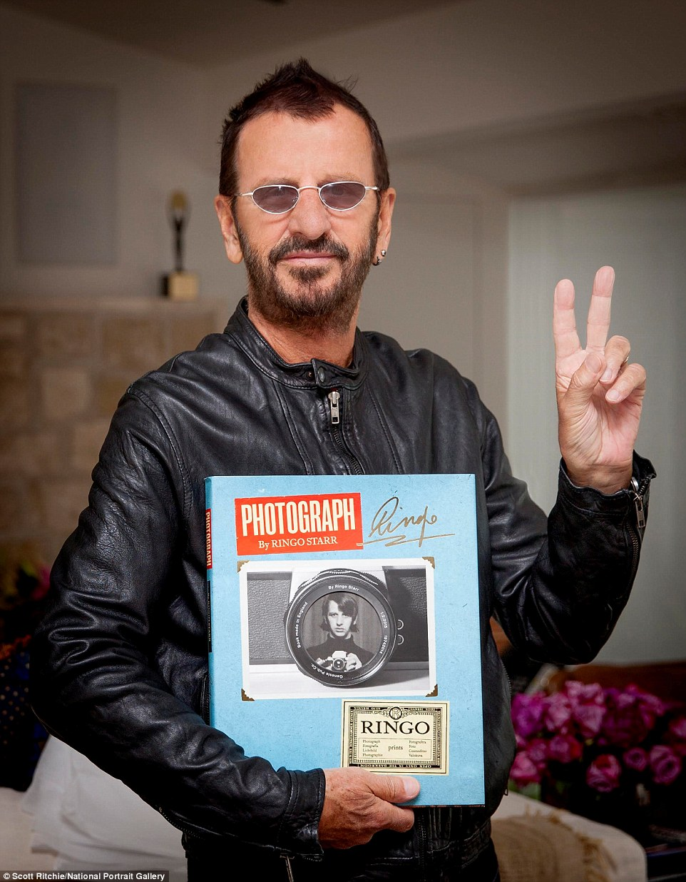 Job done: Ringo Starr pictured with a copy of the new book, Photograph. The tome is released on the 21st September