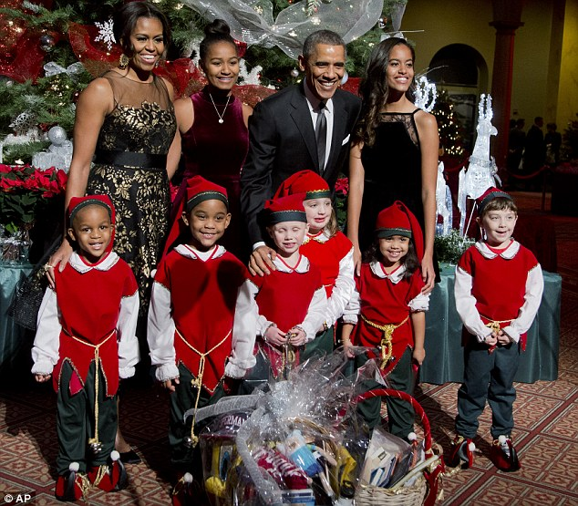 Under pressure: President Obama pose with his wife Michelle and daughters Sasha and Malia and children dressed like elves at the National Building Museum in Washington on Sunday